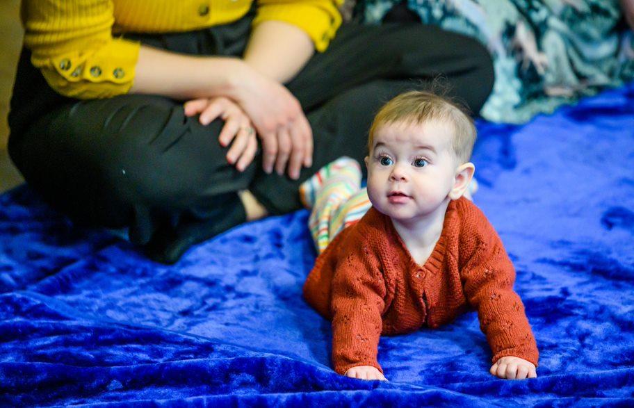 Baby crawling on a blue carpet, facing forward