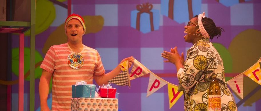 Two actors in bright clothing, the man holding bunting and the woman clapping her hands