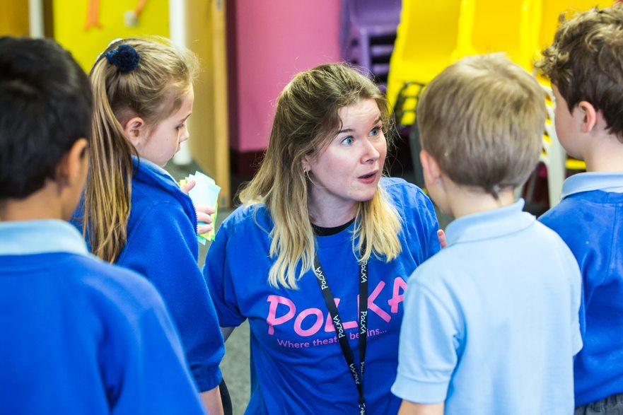 Female workshop leader in Polka t-shirt surrounded by children