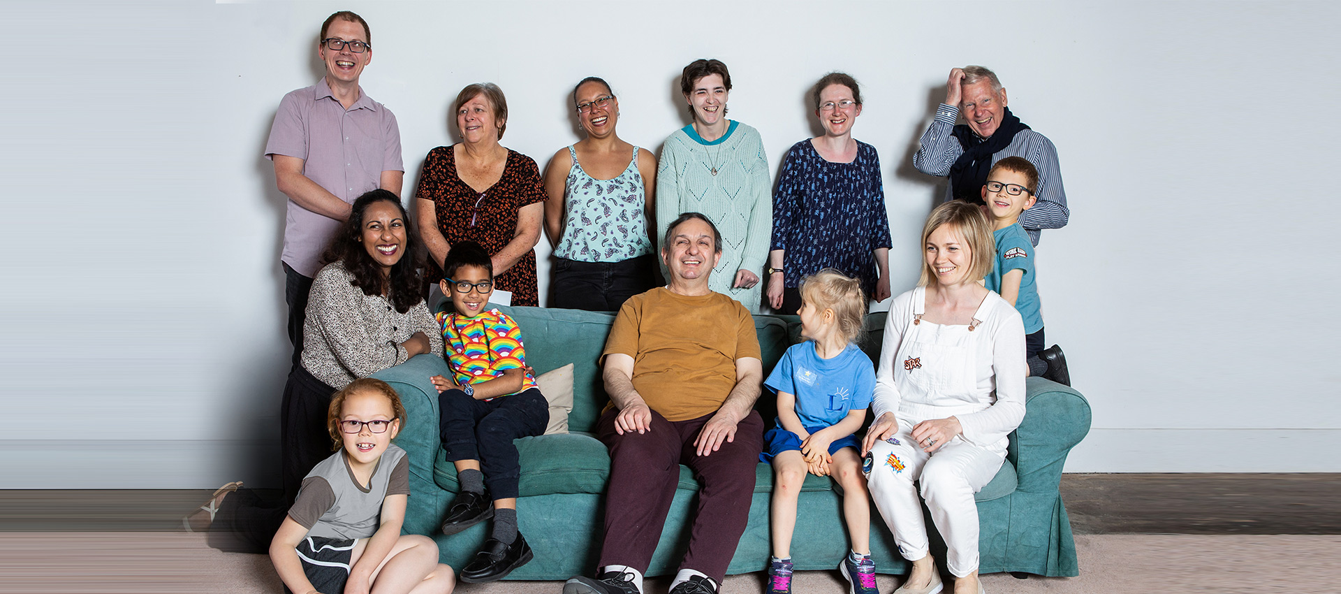 12 people laughing at the camera, a mixture of adults and children