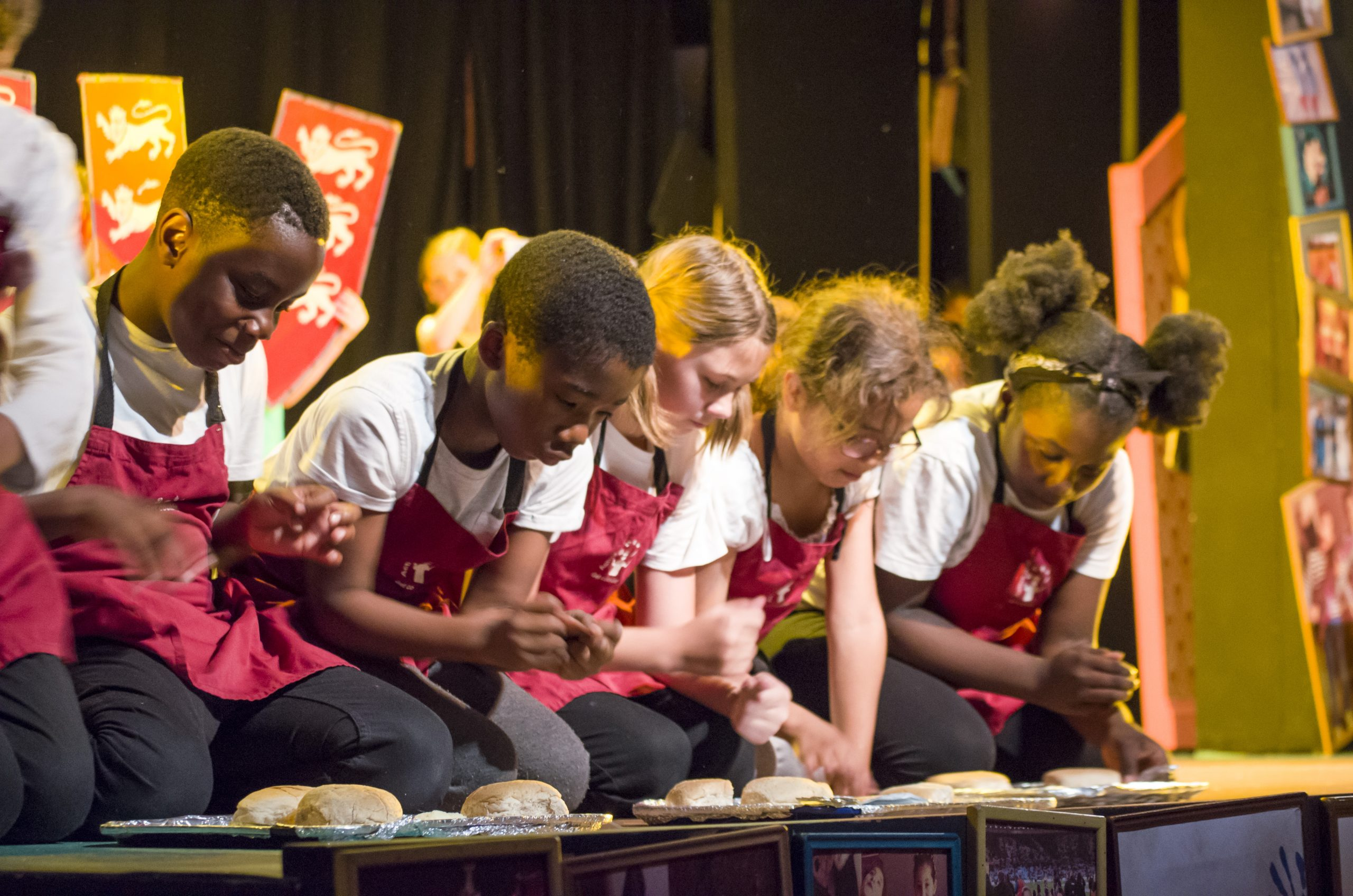 A group of children at the front of the stage kneeling over bread rolls