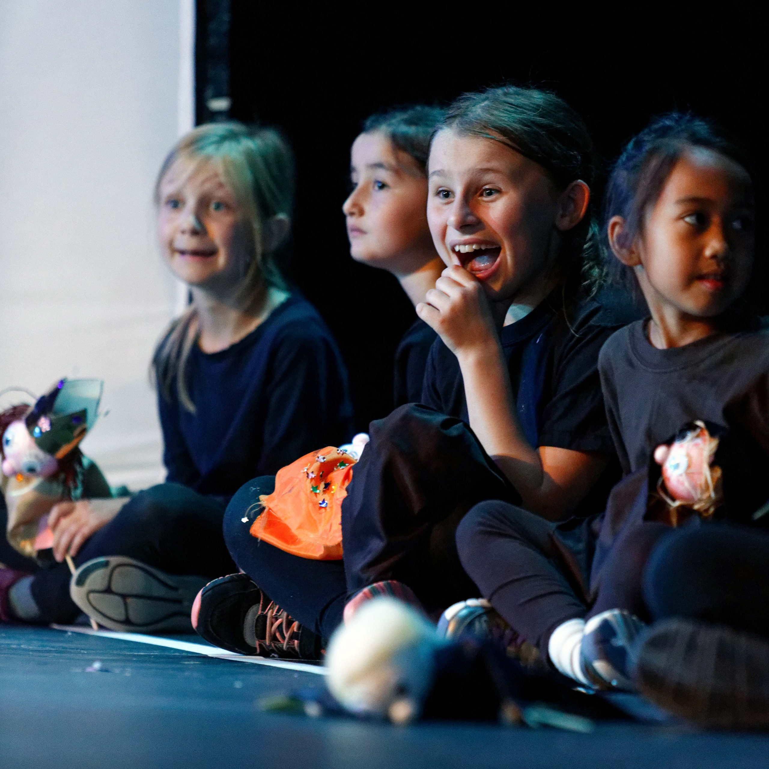 children sitting crossed legged on the floor watching a puppet show