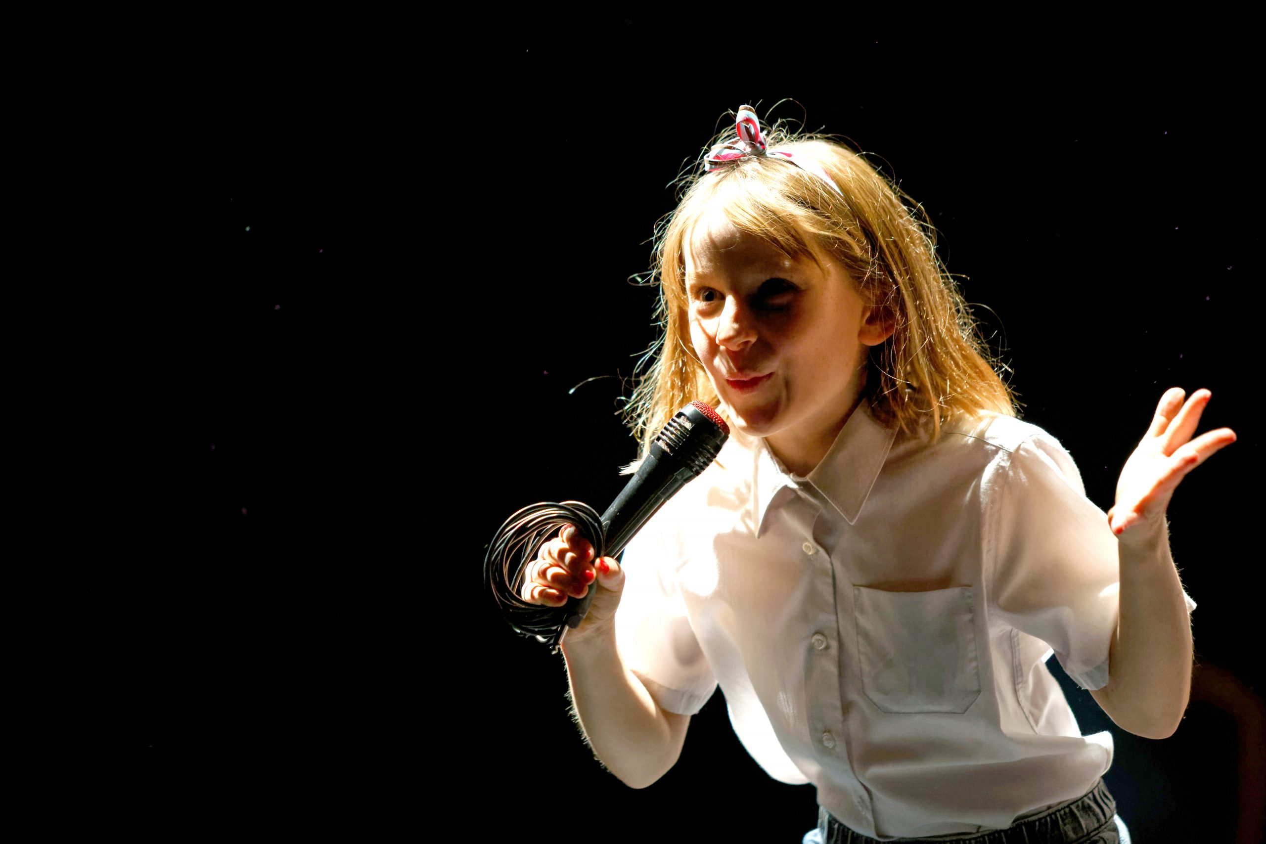Young girl talking into a microphone