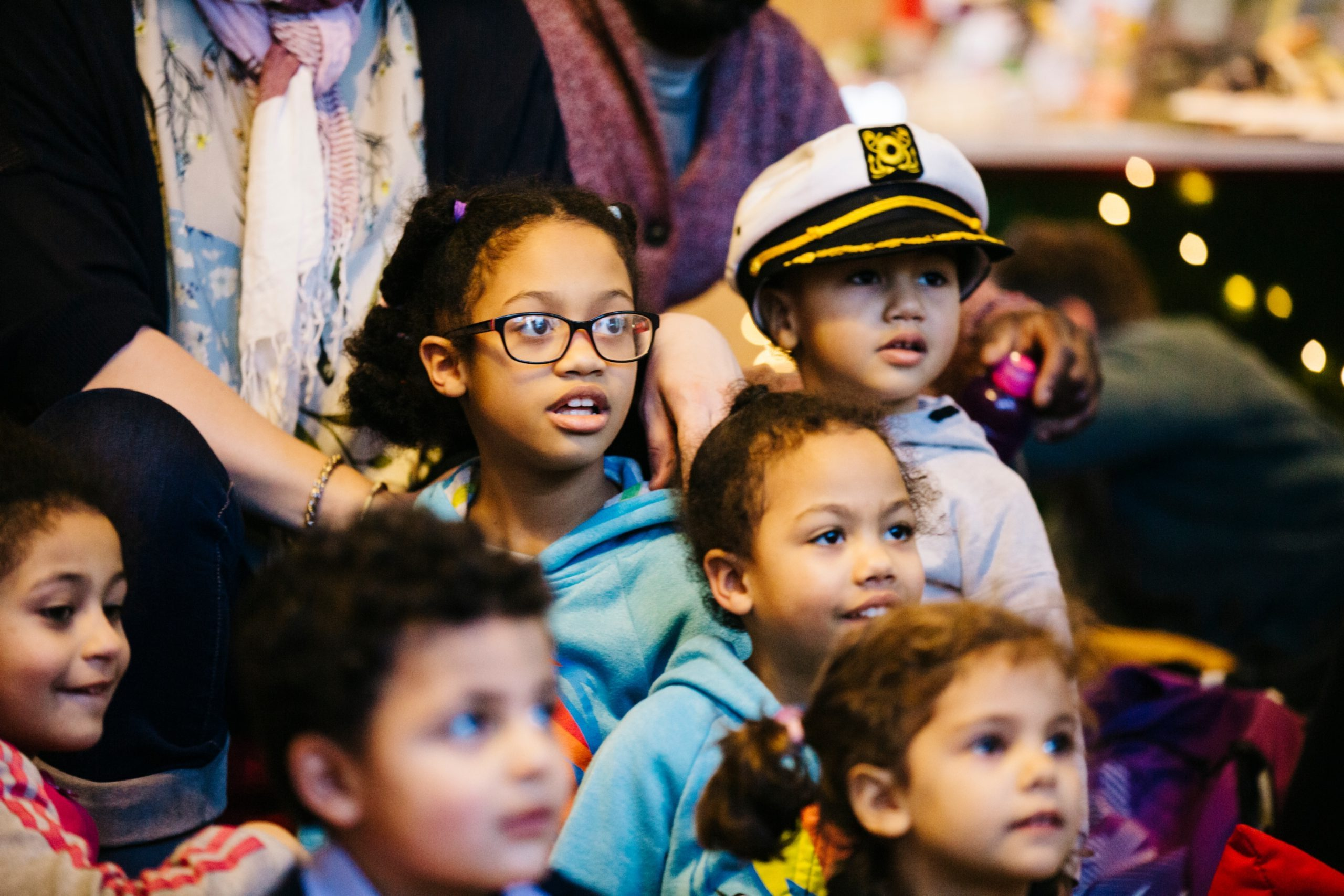 Children looking at a performance, one little boy with a sailor hat on