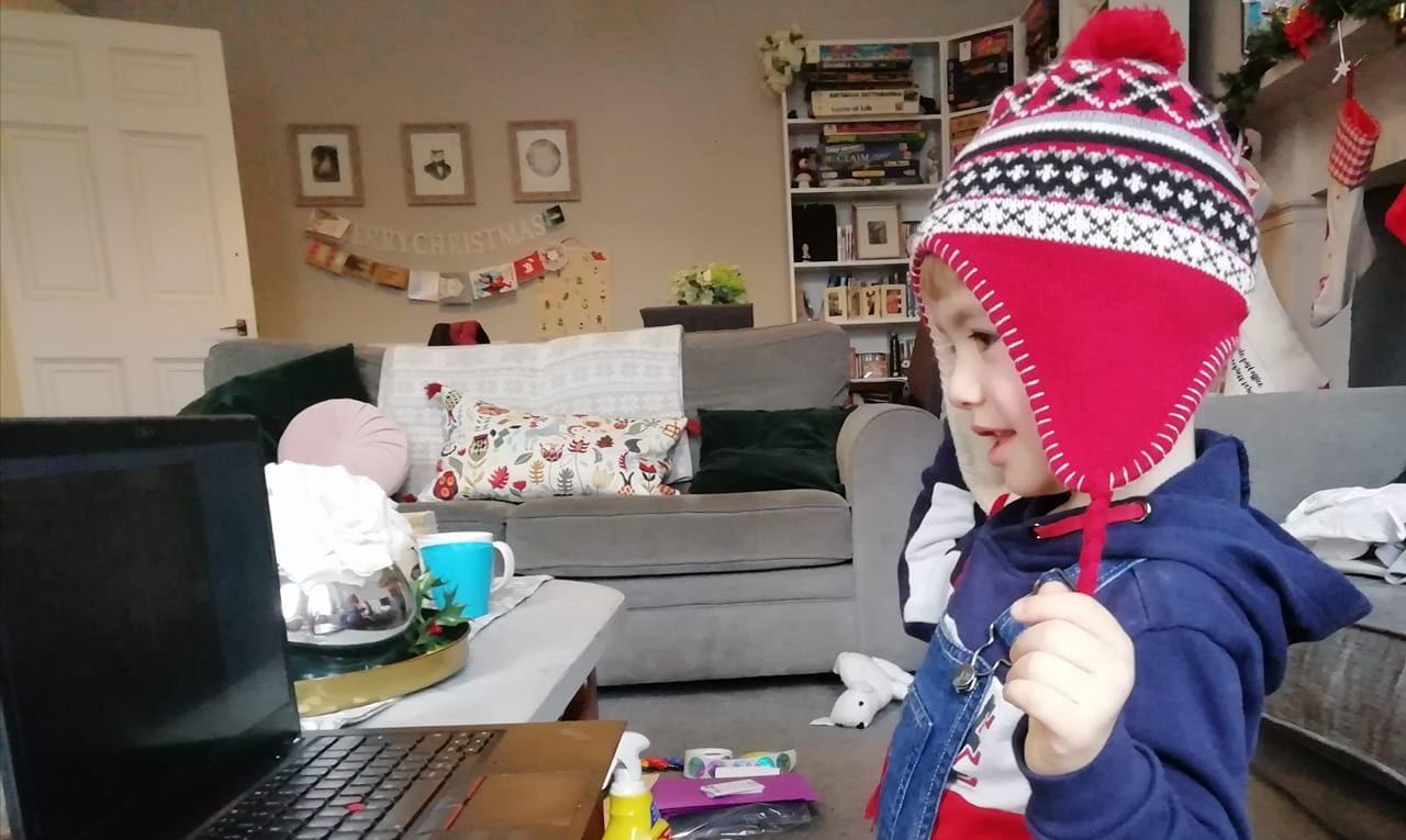 A little boy in a woollen hat watching a computer screen showing a Polka Zoom workshop