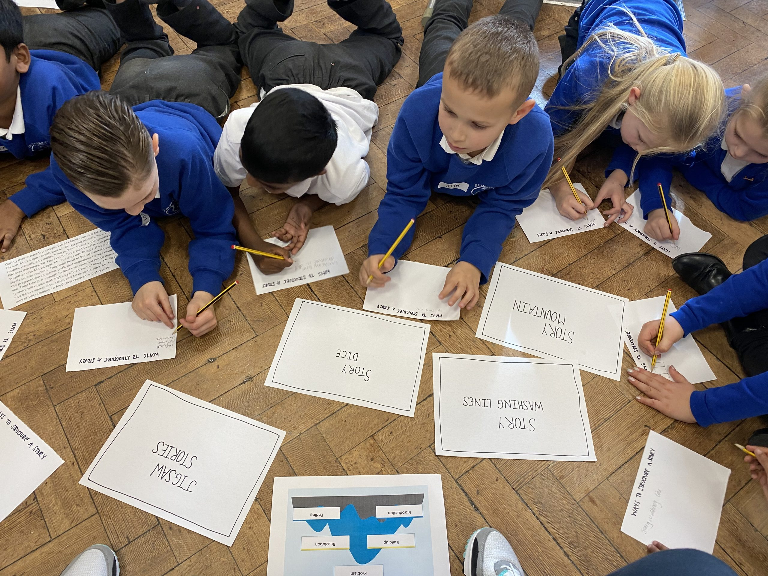 A group of children lying on their tummies writing out words