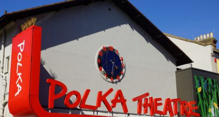 A photograph of the front of the new Polka building showing a bright Polka Theatre sign