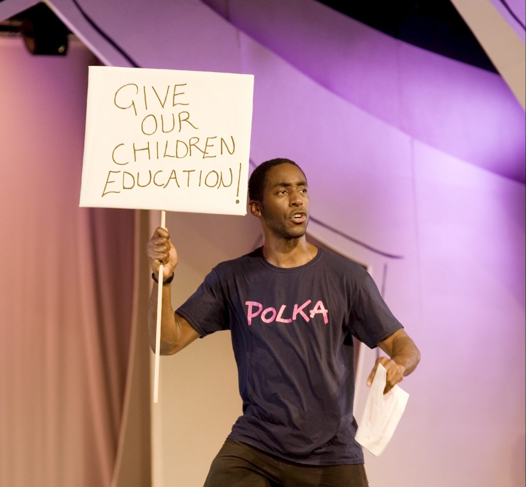 Actor on stage holding a sign which says 'give our children education'