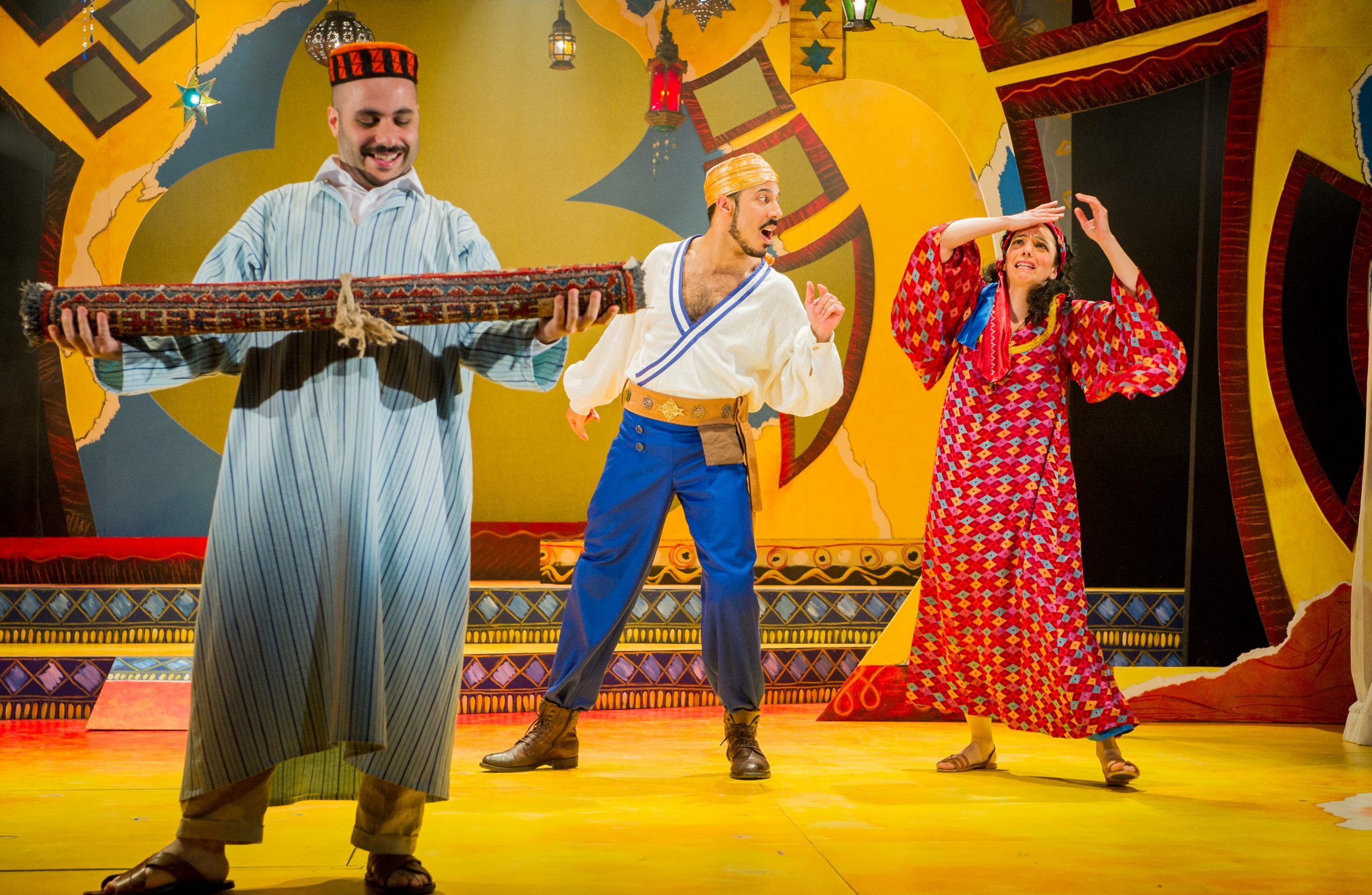 Three actors in loose Arabian clothes, one holding up a rolled up carpet