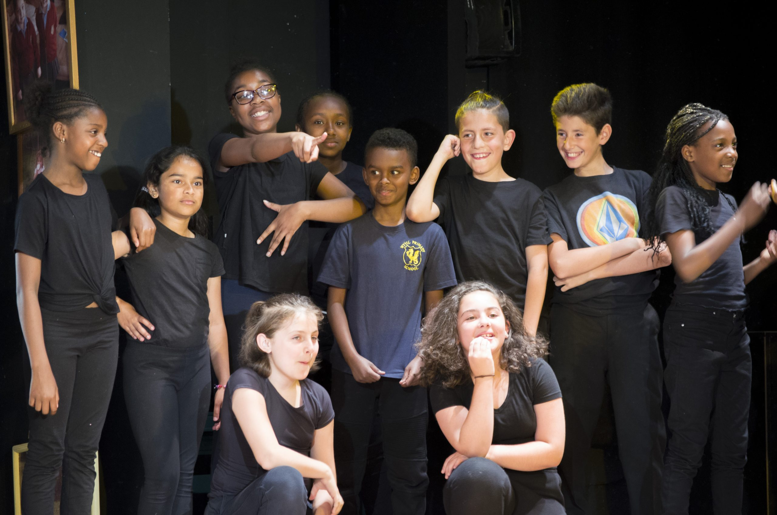 A group of children in black t-shirts form a tight group each doing a different gesture