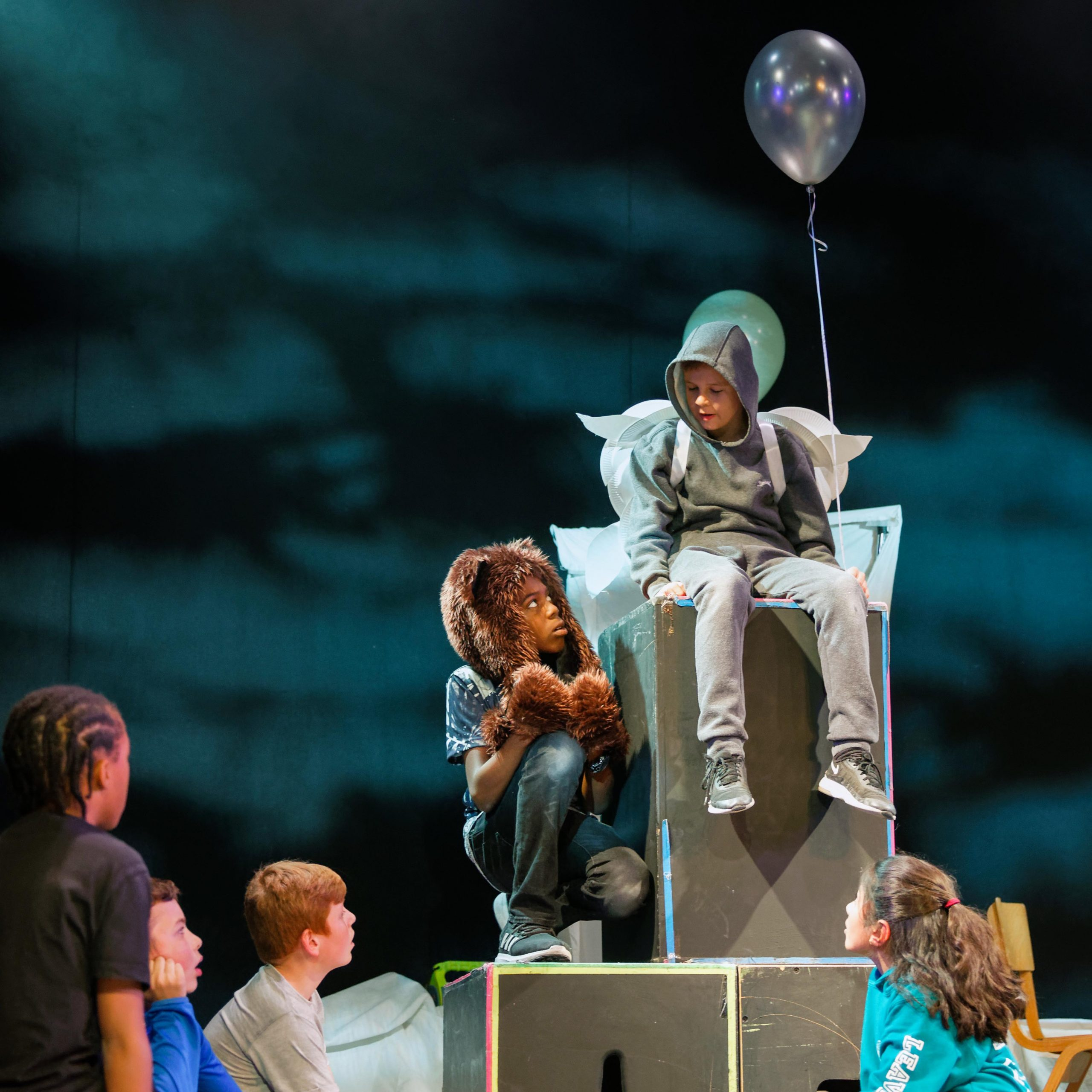2 boys performing, one sat up on chair with ballon and the other dressed as a lion kneeling