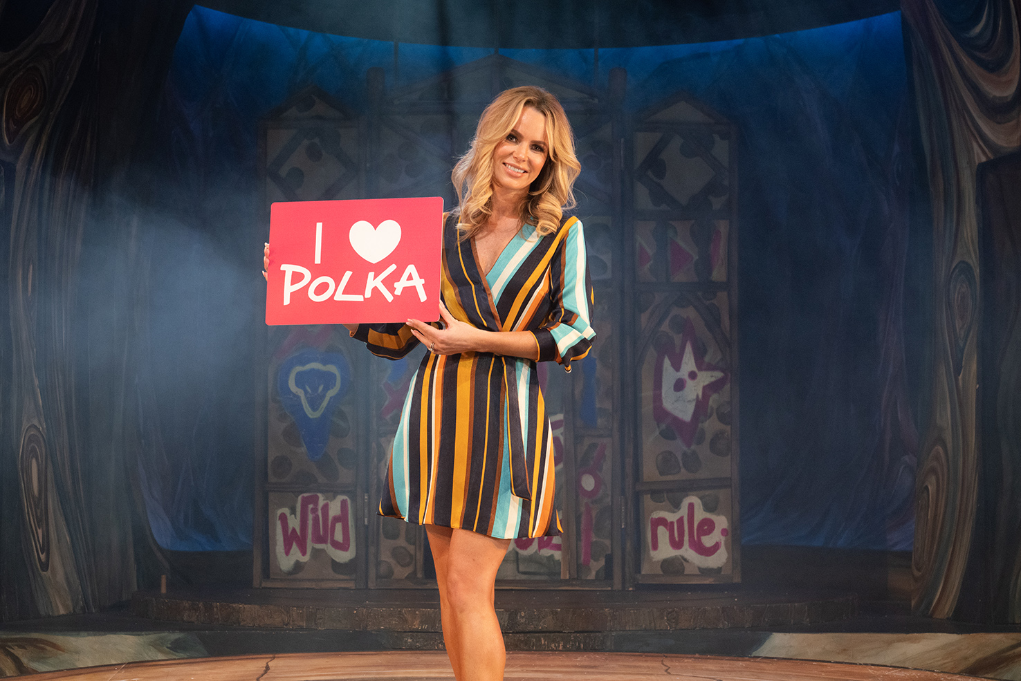 A woman holding a sign saying I Love Polka. The word love is substituted by a love heart