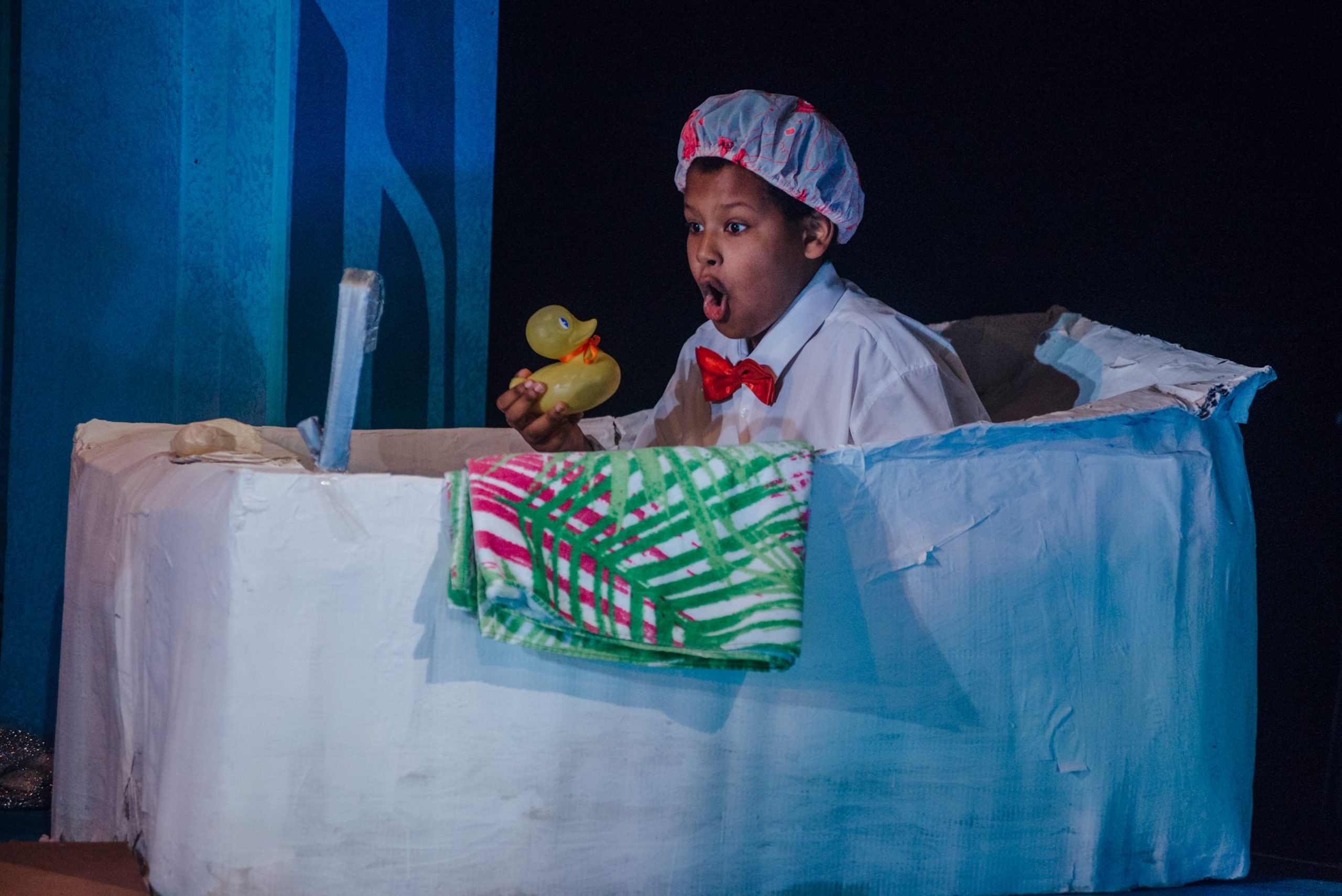 Boy holding rubber duck in a set bath on stage as part of Playhouse