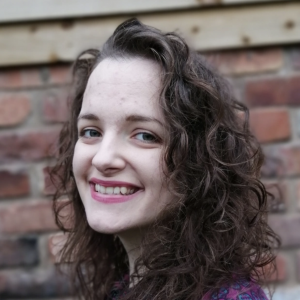 Young woman with curly brown hair smiling